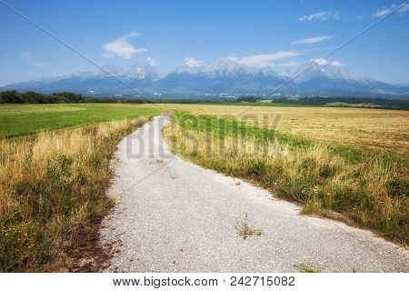 Beautiful Scene Of The Road Amoung The Yellow Grassland Mountain And Blue Sky