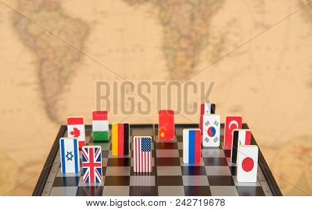 Symbols Of Countries On The Chessboard Against Against The Background The Political Map Of The World
