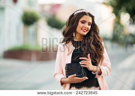 Portrait Of Attractive Brunette Girl With Long Brunette Hair Wearing Pink Jacket, Black Top And Diad
