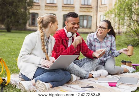 Funny jokes. Beautiful pleasant girls laughing out loud while their fellow student joking funnily in the park poster