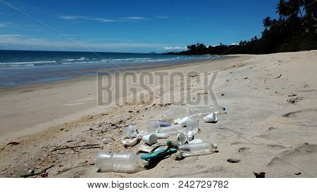 Plastic pollution on beach. Plastic water bottles, syrofoam cups and carrier bags pollute a tropical beach