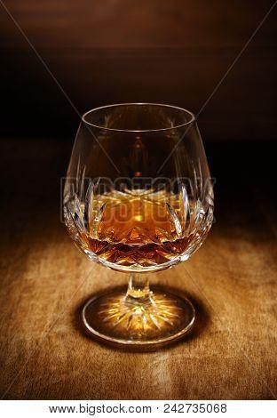 A Spotlight On A Single Crystal Glass Of Scotch Brandy, Shot On A Wooden Table Top.