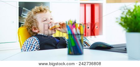 Little Caucasian Boy Playing In The Office Clerk Eating A Sandwich With Sausage In The Workplace In