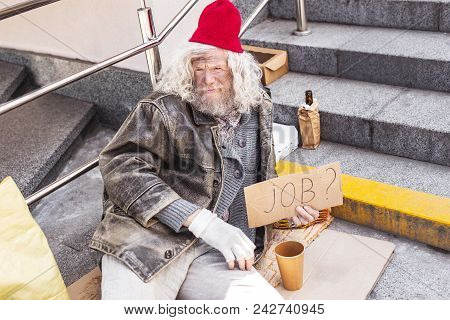 I Need A Job. Aged Homeless Man Holding A Job Sign While Needing A Job