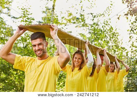 Young people in the team together wear a wooden board at a team building event