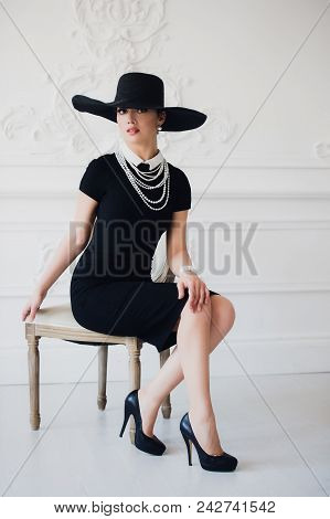 Elegant Woman In Black Dress With A Hat Sitting On A Chair.