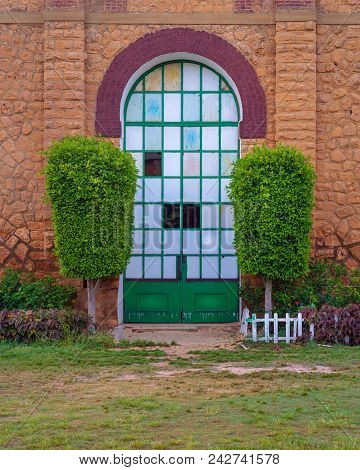 Closed Grunge Door With Green Metal Grid Framed By Two Green Bushes In Orange Colored Bricks Stone W