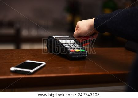 Payment With Credit Card. Edc Machine Or Terminal For Cashless Payments Near Mobile Phone. Male Hand