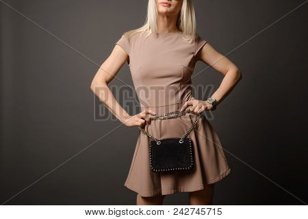Close Up Of Black Leather Bag Accessory In Hand Of Fashion Woman . Brown Short Dress
