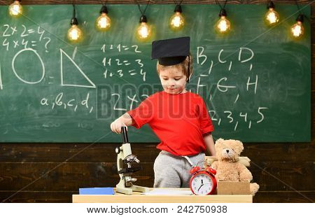 Kid Boy In Graduate Cap Near Microscope In Classroom, Chalkboard On Background. First Former Interes