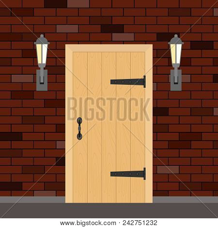 Entrance Retro Door With Torches On The Sides. Entrance Door Made Of Wood On A Brick Wall Background