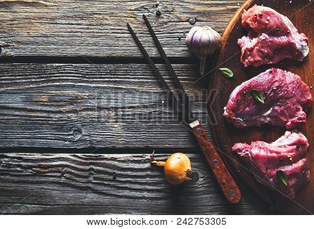 Pieces Of Meat, Steak With Spices On A Wooden Background. Food A