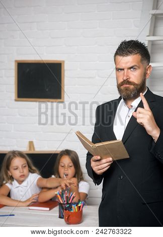 Literature Lesson And Reading Grammar Book. Literature Lesson With Small Girls And Bearded Man Teach