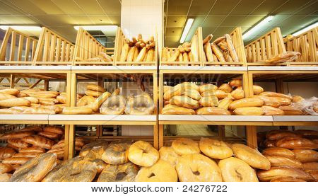 lots of fresh crisp loaves of bread on shelves in store; bread is one of main food