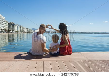 Mother And Father With Son Form Heart Of Hands. Family Travel With Kid On Mothers Or Fathers Day. Su