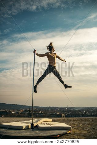 Sexy Macho Man Fly On Sky Background. Pole Dance Sport. Strong Man Dancer Workout On Pole. Athletic
