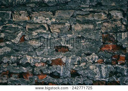 Old Weathered Brick Wall With Cracked Fallen Off Plaster. Dark Retro Grunge Background