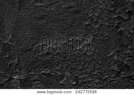 Old Black Concrete Wall With Weathered Cracked Paint. Dark Gloomy Grunge Background