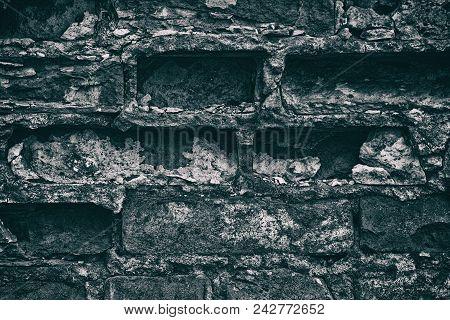 Aged Weathered Gray Brick Wall Close-up. Gloomy Dark Retro Background
