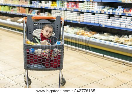 Beautiful Baby In Shopping Cart - Trolley. A Trolley With Products In Which The Child Sits. Full Car