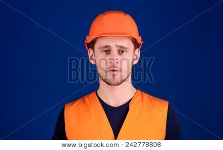 Man In Protective Helmet, Hard Hat And Working Uniform, Blue Background. Worker, Contractor, Builder