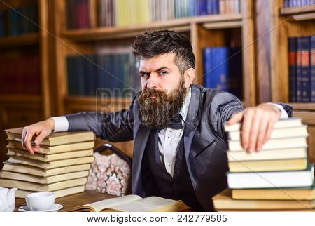 Man Sits At Table With Many Books. Mature Man Has Serious Face And Looks Confident. Successful Study
