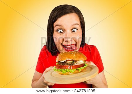 Young Woman Holds Hamburger, Smiles, Looks On Him And Licks. Isolated On Orange Background.