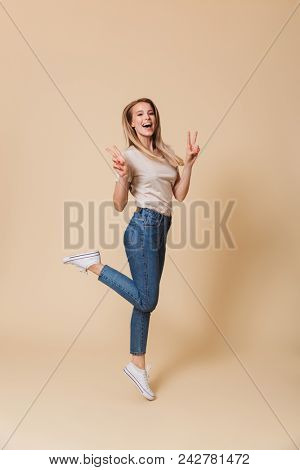 Full length image of content easygoing blond woman 20s wearing casual clothing lifting one leg and showing peace sign with two hands isolated over beige background