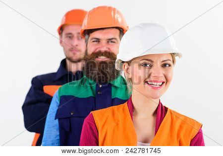 Woman And Men In Hard Hats Stand Close As Team. Team Of Architects, Builders With Happy Faces, Isola