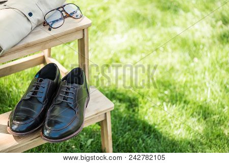 Close Up View Of Arranged Eyeglasses, Leather Shoes And Male Shirt On Wooden Stairs On Grassland