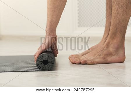 Pilates Background. Unrecognizable Man Rolling Up Yoga Mat After Training. Sport Class Before Or Aft