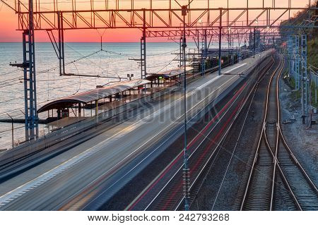 Aerial View Of The Railway Station With Motion Blurred Train On The Background Of The Sea At Sunset,