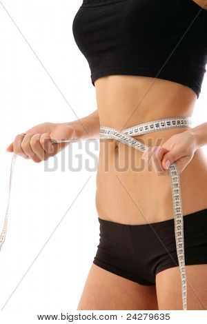 Tanned slim young woman measuring her waistline.