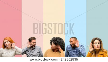 Cool group of people, woman and man holding hand near ear trying to listen to interesting news expressing communication concept and gossip