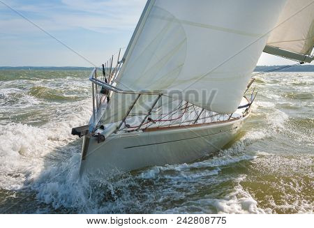 Close up of sailing boat, sailboat or yacht at sea with white sails