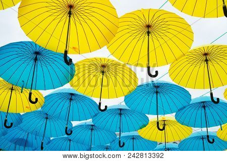 Umbrellas Float In Sky On Sunny Day. Umbrella Sky Project Installation. Outdoor Art Design And Decor