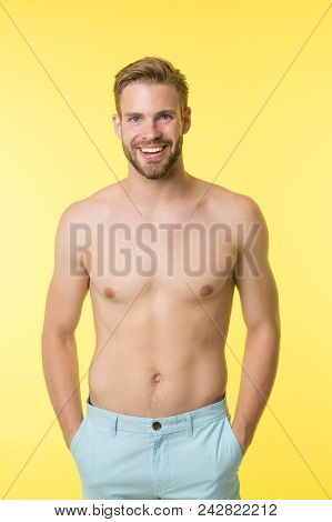 Man On Smiling Face Puts Hands In Pockets, Yellow Background. Guy With Bristle On Face And Smooth Sk