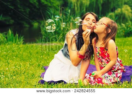 Mother And Little Girl Daughter Child Blowing Soap Bubbles Outdoor. Parent And Kid Having Fun In Par