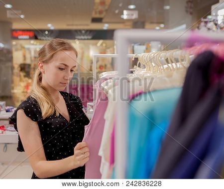 The Woman Looks At The On Clothes. Advertise, Sale, Fashion Concept. Woman Standing In Shop, Looking
