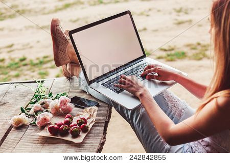 Young Woman Using And Typing Laptop Computer At Rough Wooden Table With Coffee Cup, Strawberries, Bo