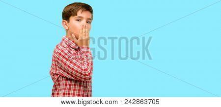 Handsome toddler child with green eyes covers mouth in shock, looks shy, expressing silence and mistake concepts, scared over blue background