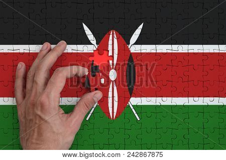 Kenya Flag  Is Depicted On A Puzzle, Which The Man's Hand Completes To Fold