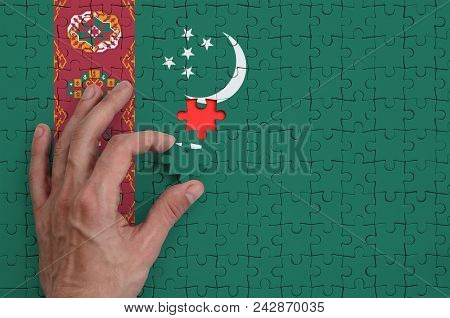 Turkmenistan Flag  Is Depicted On A Puzzle, Which The Man's Hand Completes To Fold