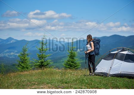 Sporty Female Backpacker With Backpack And Trekking Sticks Near Tent, On The Top Of A Hill Against B