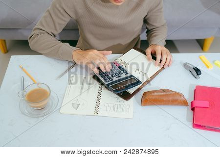 Close Up Male Hand Using Calculator And Writing Make Note With Calculate About Cost At Home Office.