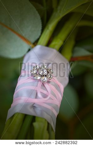 The stems of a bridal bouquet wrapped in pink chiffon, ribbon and decorated with a rhinestone broach poster