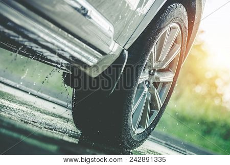 Car Driving In The Rain. Modern Rain Summer Season Tires On The Wet Pavement. Closeup Aquaplaning Ph
