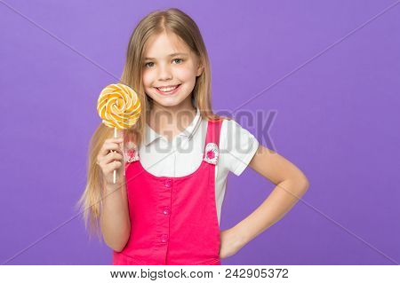 Girl Eating Big Candy On Stick Or Lollipop. Sweet Childhood Concept. Kid With Long Hair Likes Sweets