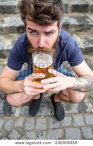 Guy having rest with draught beer. Man with beard and mustache holds beer while sits on haunches, stone stairs background. Hipster on strict face drinking beer outdoor. Draught beer concept. poster