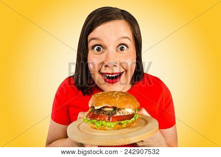 Young Woman Holds Hamburger, Smiles And Looks In Camera. Orange Background.